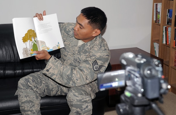 Staff Sgt. Gavin Ramos, services journeyman with the 380th Expeditionary Force Support Squadron, is video-recorded while reading a book for his children April 8, 2010, at a non-disclosed base in Southwest Asia. Sergeant Ramos was the first Airman at the 380th Air Expeditionary Wing to participate in the United Services Organization's United Through Reading program. The program allows for a deployed service member to read a book while being recorded and the book and a DVD is sent home to a child to see and follow along. Sergeant Ramos is deployed from the 154th Force Support Squadron at Hickam Air Force Base, Hawaii, and his hometown is Kapolei, Hawaii. (U.S. Air Force Photo/Master Sgt. Scott T. Sturkol/Released)