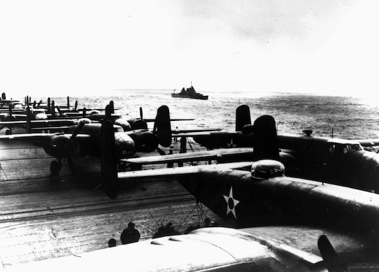 B-25 Mitchell bombers are tethered to the deck of the USS Hornet for their long trek from Calif. to Tokyo.  The bombers were modified to make them as light as possible and the tail guns were replaced with black painted broom handles to deter enemy fighters but to decrease take-off weight.  Later, newly promoted Brig. Gen James Doolittle, who led the raid, said the broom handles were surprisingly effective at deterring Japanese fighters. (Photo courtesy of 28th Bomb Wing historian's office)