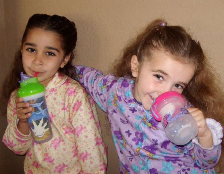 Allya (left) and Azra, children of Lt. Col. Inaam and Capt. Peter Pedalino, 59th Dental Group, use sippy cups as a training tool to learn to drink from a glass. Improper use of training cups can cause bottle mouth, a form of tooth decay, in young children caused by exposure to sugary liquids. (U.S. Air Force photo by Lt.Col. Inaam Pedalino)
