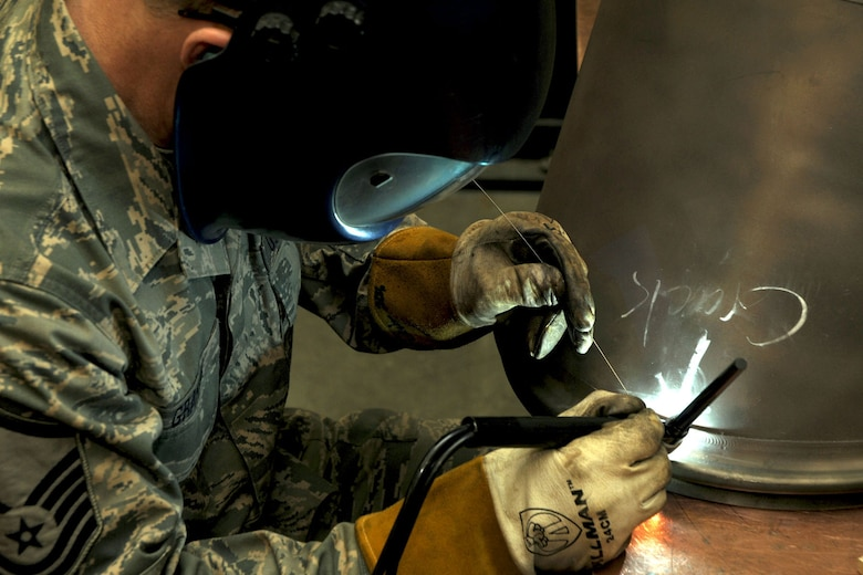 Alaska Air Guardsman MSgt Curtis Graham, a metal technology specialist,  welds a cracked tailpipe from a C-130H aircraft?s T-56 engine on April 14, 2010. Graham works for the Machine Shop in the Fabrication Section of the 176th Maintenance Squadron, Kulis Air National Guard Base, Anchorage, Alaska. The repair of the tailpipe falls under the Air Force Repair Enhancement Program (AFREP).  AFREP is a wing-level program that takes throw-away parts and makes them good as new. Unserviceable aircraft parts are carefully scrutinized to see if there is a way to salvage them for less money than it costs to replace them. (Alaska Air National Guard photo by Tech. Sgt. Shannon Oleson)