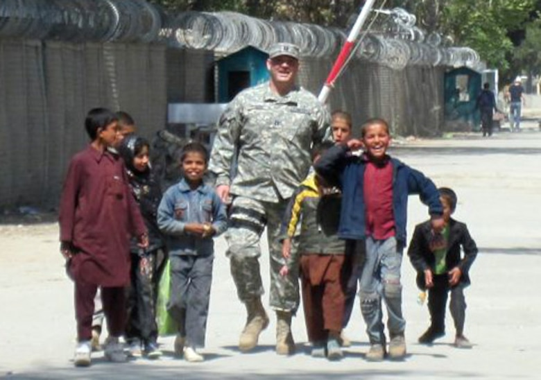 AFGHANISTAN -- Capt. Adam Pudenz, 460th Force Support Squadron, walks near a refugee camp with Afghan children. Anyone wanting to donate shoes, school supplies or other items can stop by the Airman and Family Readiness Center. (Courtesy photo)