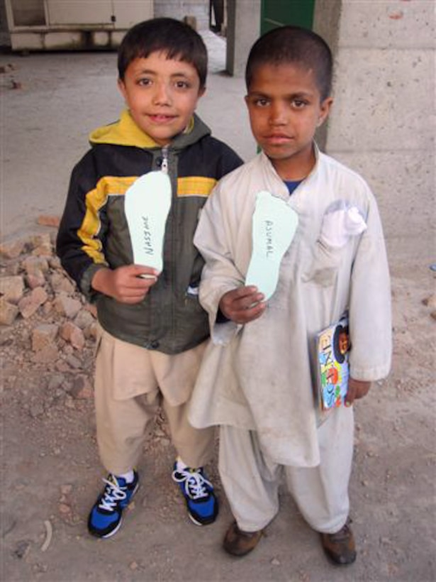 AFGHANISTAN -- Nasime and Ajumal, two Afghan refugee children, mug for Capt. Adam Pudenz, 460th Force Support Squadron. The children are wearing donated shoes collected by the Company Grade Officer Council. (Courtesy photo)