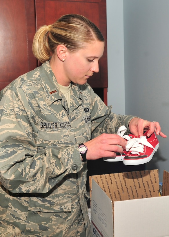 BUCKLEY AIR FORCE BASE, Colo. -- 2nd Lt. Jessica Gruver Koefod, 460th Force Support Squadron, packs donated shoes for shipment to children in Afghanistan. The Company Grade Officer Council is still accepting footware donations. (U.S. Air Force photo by Airman 1st Class Manisha Vasquez)