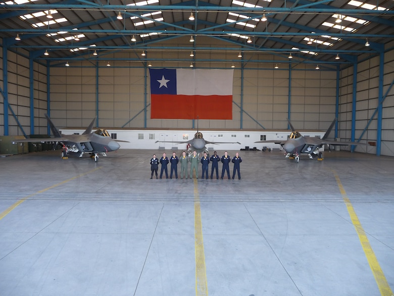 SANTIAGO, Chile -- Air Combat Command's F-22 Raptor Demonstration Team pose for a media photo opportunity in front of Chilean Air Force F-16 and two F-22 Raptors.  The Demonstration Team performed during the FIDAE air and trade show in Santiago, Chile 20-28 March.  Also during the event, the team met with local community leaders, hosted children from various charitable organizations and visited a hospital for ill children.