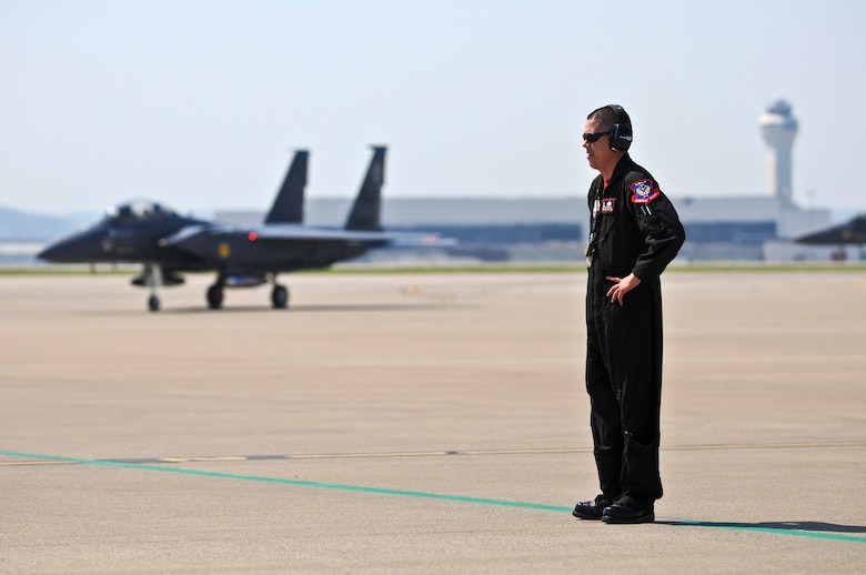 Staff Sgt. Gabriel Castillo, a U.S. Air Force crew chief with the 4th Fighter Wing at Seymor Johnson Air Force Base, N.C., stands by to marshall an F-15 Strike Eagle to its parking spot on the Kentucky Air National Guard Base flightline in Louisville, Ky., on April 15, 2010. The F-15 will participate in this weekend's Thunder Over Louisville airshow. (U.S. Air Force photo by Senior Airman Maxwell A. Rechel)