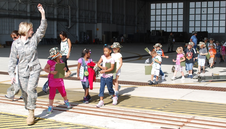 Tech. Sgt. Monica Gonzales of the Airman & Family Readiness Center acted as a troop leader for the Kids Understanding Deployment Operations event April 10. Here she leads the junior deployers out of a hangar, where they toured a HH-60 Pave Hawk