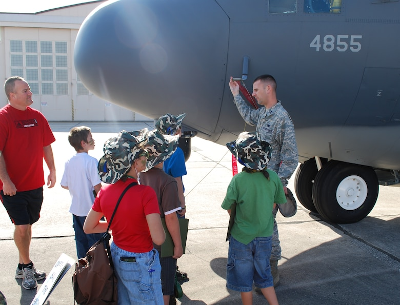 Capt. Dan Posch, a maintenance operations officer with the 920th Rescue Wing, describes a HC-130 aircraft to a group of junior deployers during the Kids Understanding Deployment Operations event April 10. The KUDOS program is part of the Year of the Air Force Family and helps children learn about deployments. (U.S. Air Force photo/Senior Airman David Dobrydney)