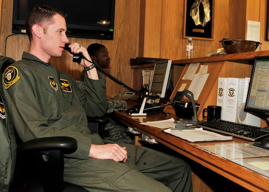 Capt. Mike Conrad, 493rd Fighter Squadron Operations Desk supervisor, answers the phone as Senior Airman Patrick Moton, Aviation Resource Management System manager, inputs data at the 493rd FS Operations Desk on March 26, 2010. (U.S. Air Force photo/Airman 1st Class Tiffany M. Deuel)