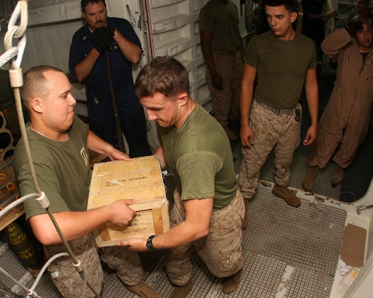 Sgt. Peter Goitia-Ojeda, (left) administrative chief for Alpha Company, Battalion Landing Team 1st Battalion, 9th Marine Regiment, 24th Marine Expeditionary Unit, passes a box of .50 caliber rounds to a line of Marines relocating ammunition from a Navy ammunition supply area aboard USS Ashland April 16, 2010. The largest ammunition load transported from USS Ashland to shore for upcoming training events during the 24th MEU's deployment.  The 24th MEU is currently on a seven month deployment, and is the theatre reserve force for Central Command.  (U.S. Marine Corps photo by Gunnery Sgt. Chad R. Kiehl)