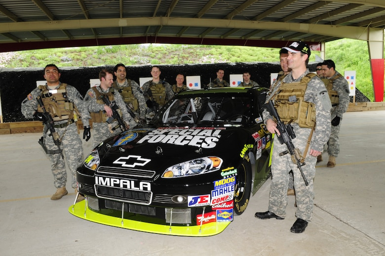 Suited up with Army National Guard equipment and uniform (except for cap and boots), NASCAR driver Jeff Gordon joins National Guard Security Forces Soldiers with his #24 car sporting a new paint scheme and graphics honoring the elite Soldiers, in Texas, on April 15, 2010. (U.S. Air Force photo by Senior Master Sgt. Mike Arellano/Released)