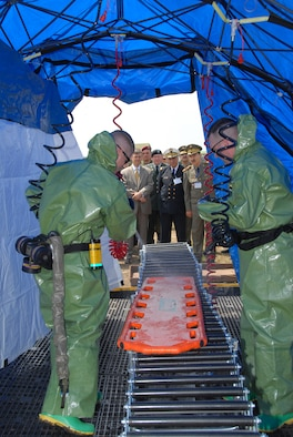 U.S. Ambassador to Tunisia Gordon Gray, along with several members of the U.S. and Tunisian armed forces, watch Air Force Master Sgts. Shane Larson and Jeremy Nash, medical technicians with the 153rd Medical Group, 153rd Airlift Wing, Wyoming Air National Guard, demonstrate the capabilities of the REEVES Decontamination System.  Service members from several states are in Tunisia participating in the MEDLITE-10 exercise at Kharrouba Air Base, Bizerte, Tunisia.  (USAF Photo by Master Sgt. Paul Mann/Released)