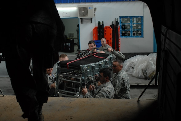 Several service members from Wyoming, Arizona, Nevada, and Illinois help load parts of a decontamination system onto the bed of a truck at Kharrouba Air Base, Tunisia during the MEDLITE-10 exercise. These American service members are in Tunisia as part of the U.S. partnership program with the North African nation, exchanging medical treatment practices and programs. (USAF Photo by Master Sgt. Paul Mann/Released)
