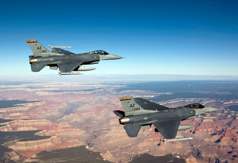 Capt. Bob Peel, left, and Lt. Col. Tony Adamo, right, F-16 instructor pilots from the 162nd Fighter Wing, fly over the Grand Canyon while supporting Operation Noble Eagle's air sovereignty alert mission. The Arizona Air National Guard alert unit recently earned the 2009 Air Sovereignty Alert Unit of the Year award. (Photo by James Haseltine, High-G Productions)