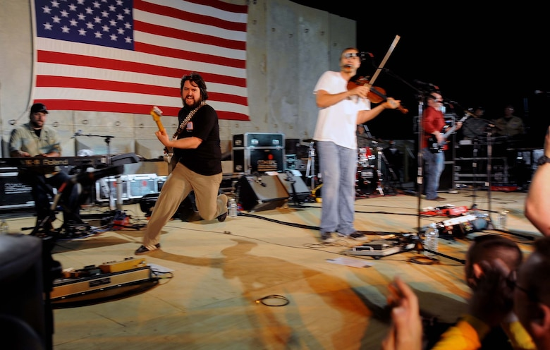 "Clay Cook, a member of the Zac Brown band, runs across the stage during the performance of ""Devil Went Down to Georgia"" for a crowd of deployed personnel in Holt Stadium at Joint Base Balad, Iraq, April 18, 2010. The Grammy nominated band is touring various bases throughout Southwest Asia to perform for the troops rather than attend this year's Academy of Country Music Awards for which they were nominated. (U.S. Air Force photo by Master Sgt. Linda C. Miller/Released)"