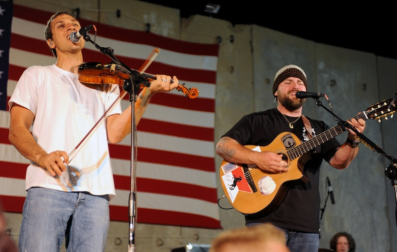 Zac Brown (right) and Jimmy De Martini, members of the Zac Brown band perform for a crowd of deployed personnel at Holt Stadium at Joint Base Balad, Iraq, April 18, 2010. The Grammy-nominated band is touring various bases throughout Southwest Asia to perform for the troops rather than attend this year's Academy of Country Music Awards for which they were nominated for several awards. (U.S. Air Force photo by Master Sgt. Linda C. Miller/Released)