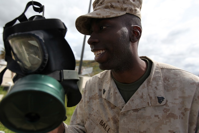 Cpl. Taavon Ball, 23, a field wireman from Baltimore puts his M40A1 gas mask on before entering the 33 area gas chamber. Marines from 9th Communication Battalion, 1st Intelligence Battalion and 1st Radio Battalion took part in an annual confidence mask training exercise to learn how to use their gas mask properly and what to do when faced with a chemical attack. (U.S. Marine Corps photo by Lance Cpl. John M. McCall)
