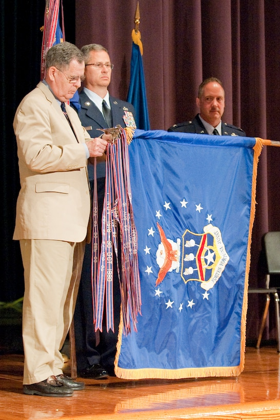 Dennis M. McCarthy, assistant secretary for Reserve Affairs (far left), pins a streamer representing the 123rd Airlift Wing's 14 Air Force Outstanding Unit Award onto the wing's guide-on during a ceremony held April 17, 2010, at Louisville Male High School in Louisville, Ky.  The 123rd Airlift Wing has now won more Air Force Outstanding Unit Awards than any other unit in the Air National Guard, officials said. Also pictured (from left to right) are Chief Master Sgt. James Smith, state command chief master sergeant for the Kentucky Air National Guard; Col. Gregory Nelson, commander of the 123rd Airlift Wing; and Chief Master Sgt. Curtis Carpenter, command chief master sergeant of the 123rd Airlift Wing. (U.S. Air Force photo/Maj. Dale Greer)