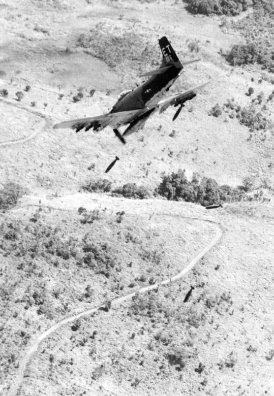 A single-seat A-1H aircraft flies through the air.