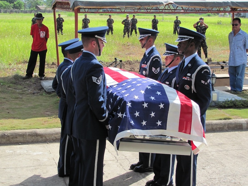 Members of the Kadena Air Base Honor Guard hold the flag-draped casket of Tech. Sgt. Raymond Natividad during a funeral detail. In the background, the firing team from the Philippine army prepares to render the 21-gun salute, finishing out the full honors ceremony. (U.S. Air Force photo / Tech. Sgt. Brian Roberts)