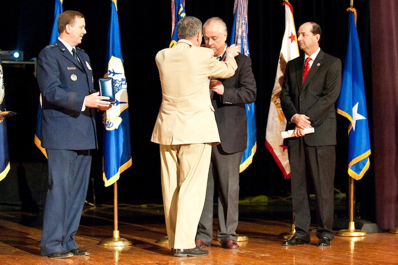 Dennis M. McCarthy, assistant secretary of defense for Reserve Affairs (left), presents State Sen. David L. Williams with a Department of Defense Centers of Influence Award during a ceremony held April 17, 2010 at Louisville Male High School in Louisville, Ky. The award recognizes individuals who have been especially supportive of military service members since Sept. 11, 2001. (U.S. Air Force photo/Maj. Dale Greer)