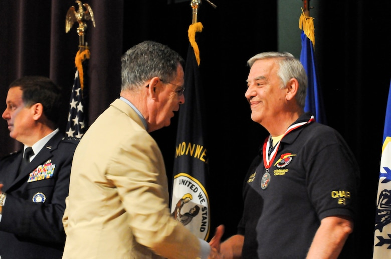 Dennis M. McCarthy, assistant secretary of defense for Reserve Affairs (left), presents Mr. Wayne Hettinger, producer of the annual Thunder Over Louisville Air Show, with a Department of Defense Centers of Influence Award during a ceremony held April 17, 2010 at Louisville Male High School in Louisville, Ky. The award recognizes individuals who have been especially supportive of military service members since Sept. 11, 2001. (U.S. Air Force photo/Tech. Sgt. Dennis Flora)