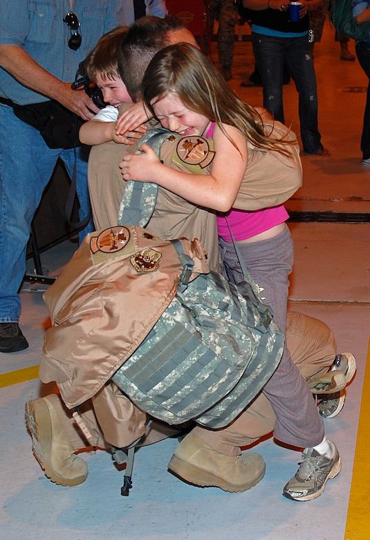 Maj. Steve Jones, 121 FS Pilot, has his hands full with daughter Clara and son Marc upon arriving home from deployment in support of Operation Iraqi Freedom, April 6. (U.S. Air Force photo by Tech Sgt. Tyrell Heaton/Released)