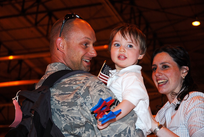 Tech Sgt. Jeff Johnson, 201 FS Weapons Specialist, receives a warm welcome home from girlfriend Deonne O'Connor and her son, Tristan; the Airman returns from an AEF rotation in support of Operation Iraqi Freedom, April 6. (U.S. Air Force photo by Tech Sgt. Tyrell Heaton/Released)