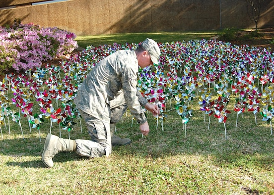 Airman 1st Class Philip Mazzie, 81st Medical Operations Squadron mental health flight family advocacy program staff, places pinwheels in the front of the hospital April 13.  (U.S. Air Force photo by Steve Pivnick)