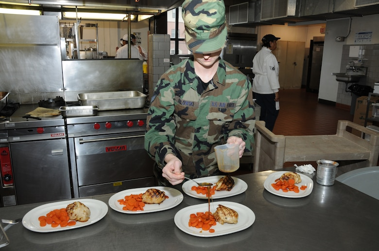 Senior Airmen Evelyn Orlowski from Team A prepares the plate for the judges. Team A's meal was Caramelized apple stuffed chicken breast with fontina and bing cherries served with glazed carrots. (U.S. Air Force photo/Staff Sgt. Peter Dean)