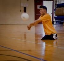 Cpl. Ray Hennagir, athlete with All-Marine Warrior Games Team, prepares to hit a volleyball during training camp practice, April 28 at the Base Gym. Sitting volleyball is one of the few Warrior Games heavily dependent on teamwork. Not only overcoming individual challenges but overcoming them as a team in order to win.