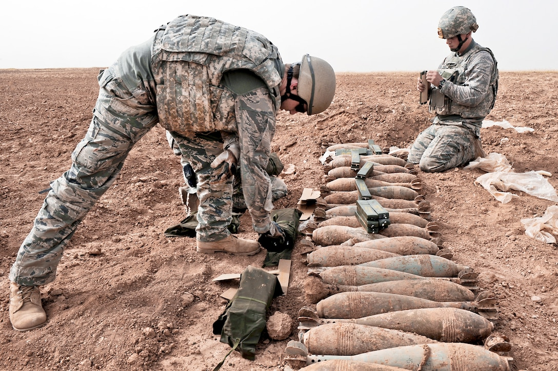 Staff Sgt. Matt Skelton (left) and Staff Sgt. Charles Hodge prepare to detonate 120-mm Russian mortar rounds April 13, 2010, in a desolate area of Iraq.  The two explosive ordnance disposal NCOs are with the 506th Civil Engineer Squadron at Joint Base Balad, Iraq. (U.S. Navy photo/Petty Officer 2nd Class Matthew D. Leistikow)