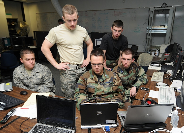 Cadet 3rd Class Tyler Schultz and Cadets 1st Class Anthony Blankenberger, Benjamin Bruckman, Jase Garcia and Jesse Lind gather around to watch proceedings during the National Security Agency's 2010 Cyber Defense Exercise at the U.S. Air Force Academy April 22. Cadets in the exercise built a network and had to defend it from NSA aggressor teams' attacks. (U.S. Air Force photo/Rachel Boettcher)