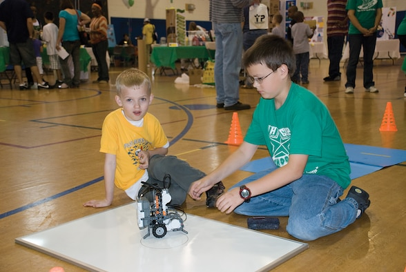 SCOTT AIR FORCE BASE, Ill. -- Joe Phillips, 11, (right) shows Ethan Bortvit, 7, how to operate a robot.  Joe is a member of the Shooting Stars 4-H club, which meets in Fairview Heights, Ill. (U.S. Air Force Photo by Steve Berry)