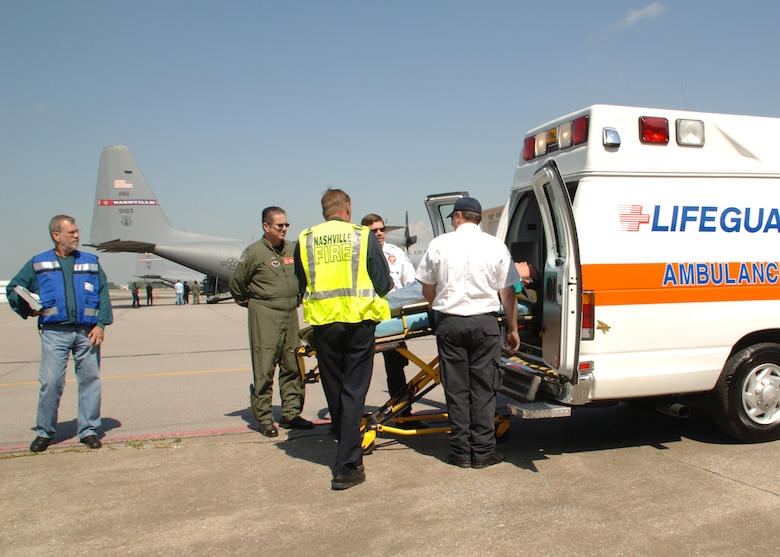 A patient is loaded into an ambulance to be transported to a nearby hospital. Once the patients reach the hospital, the drill is over. They are delivered by a bus back to the base so they can return home.