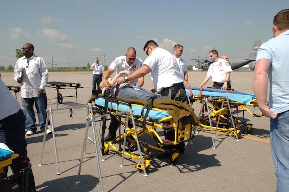 Ambulance staff fasten a volunteer 'victim' to a gurney.