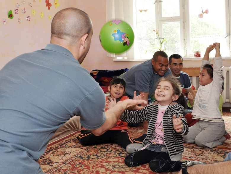 Master Sgt. Jeff Villemarette plays with children April 27, 2010, at the Nadjeshda Children's Center in Kyrgyzstan. Nadjeshda is home for 60 children and teenagers who are disabled in different ways. Sergeant Villemarette is assigned to the Transit Center at Manas. (U.S. Air Force photo/Staff Sgt. Carolyn Viss)