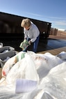 Laurie Baker, Booz Allen Hamilton environmental consultant, pulls cardboard April 22 from a bag of trash headed for the landfill that could have been recycled. Ms. Baker performs trash audits on Peterson AFB to show how much material could be recycled. The Earth Day audit found 45.8 pounds of plastics, 56.6 pounds of white paper, 21.2 pounds of aluminum and 13.8 pounds of cardboard that could have been recycled. The results will be used by the 21st Civil Engineer Squadron and building managers to design recycling programs. (U.S. Air Force photo/Rob Bussard)