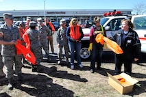 Cindy Litteral (right), 21st Civil Engineer Squadron fire chief, hands out safety vests and orange garbage bags to Earth Day volunteers who picked up trash along Highway 24 outside the north gate on Peterson AFB April 22. Chief Litteral has orchestrated trash pick-up days on and around Peterson AFB for years. This year more than 50 volunteers collected about 3,500 pounds of trash, which was picked up by Colorado Springs crews. (U.S. Air Force photo/Rob Bussard)
