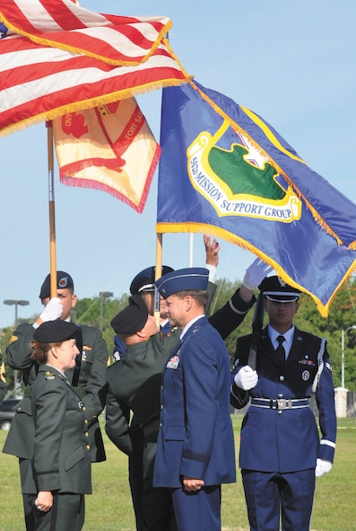 The 502nd Mission Support Group flag unfurls behind Col. Mary Garr, 502 MSG/Garrison commander and Air Force Brig. Gen. Leonard Patrick, commander of the 502nd Air Base Wing, after the group's official activation at Fort Sam Houston's MacArthur Parade Field April 26.