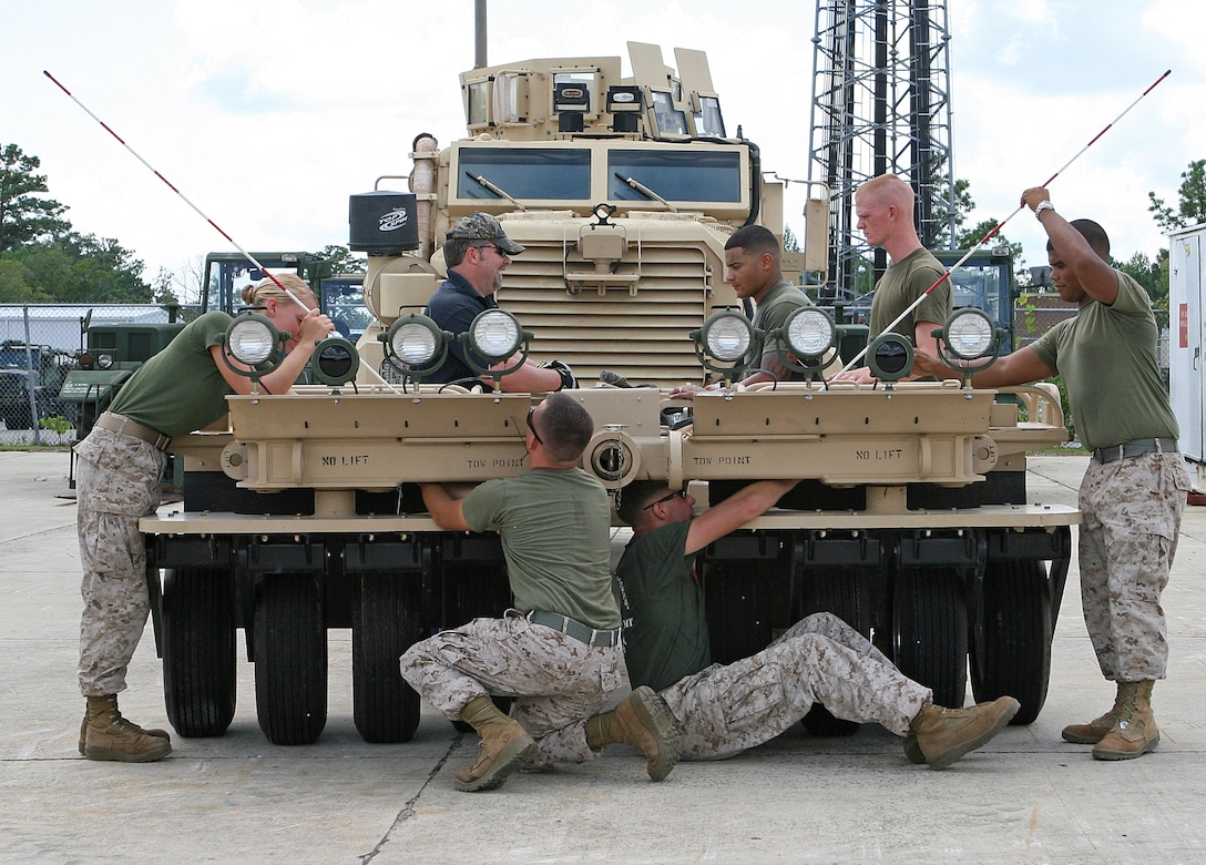 Marines from various stations on the East Coast work as a team to maintain a Panama City Generation III Mine Roller System attached to a Mine Resistant Ambush Protected tactical vehicle aboard Marine Corps Base Camp Lejeune, N.C., Aug. 2, 2010. The Marines took part in a three-day training evolution to learn how to maintain and operate the newly upgraded mine roller system that is currently being employed by the Marine Corps in Afghanistan.