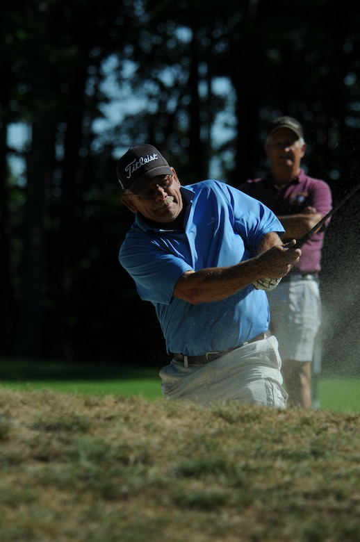 NH Air National Guard Master Sergeant William Gammon hits his golf ball out of a bunker during the 46th Annual NH National Guard Golf Classic 2010 tournament held at The Oaks golf link, Somersworth, NH, July 26, 2010.  Master Sergeant (retired)  Earl Andrews watches from the background.  (released/photo by Aaron P. Vezeau