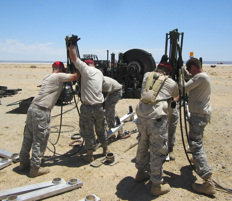 Airmen from 823rd and 820th RED HORSE perform stakeline installation on the mobile aircraft arresting system.  More than 150 66-inch stakes were installed to keep the MAAS in place. The team is made up of Airmen from Hurlburt Field, Fla. and Nellis Air Force Base, Nev.  The RED HORSE team installed the MAAS for the on-going Joint Strike Fighter brake testing. (Air Force photo)
