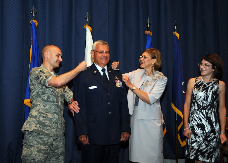 "Maj. Gen. James Kwiatkowski is pinned by his son 107th AW Tech. Sgt. Andrew Kwiatkowski and the general's wife Ranea on right as his other daughter Nicole Dabby looks on during a ceremony held Aug. 4 at Scott AFB. ""This is a sacred trust and I will do my best to be effective in the trust placed in me today,"" said the general. (U.S. Air Force photo/Staff Sgt. Peter Dean)"