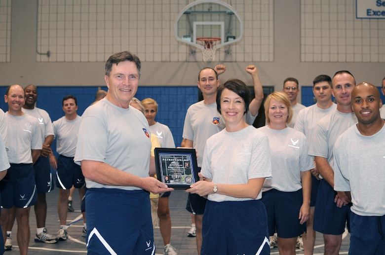 McGHEE TYSON AIR NATIONAL GUARD BASE, Tenn. -- Master Sgt. Bonnie S. McGuffin, EPME instructor, right, receives the TEC Patriot Award from Col. Richard B. Howard, commander, left, during the commander's monthly fitness training session at Wilson Hall on the campus of The I.G. Brown Air National Guard Training and Education Center here, July 28, 2010.  (U.S. Air Force photo by Master Sgt. Kurt Skoglund/Released)