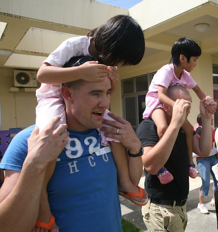 Marines with the 31st Marine Expeditionary Unit carry children on their shoulders and line up for a relay race during their visit to Nagomi Children's Orphanage, August 6. Marines from Marine Corps Base Camp Schwab and Camp Hansen often visit this orphanage to spend time with the children. (Photo by Lance Cpl. Tyler C. Vernaza)