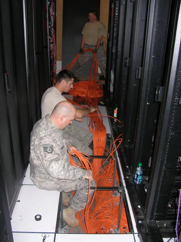 From front to back, Staff. Sgt. Sean Belmonte, Staff Sgt Lake Bouder and Senior Airman Michael Johnson, cable and antenna technicians, installed more than 40,000 feet of CAT 5 cable, 35,000 feet of fiber-optic cable and terminated more than 3,000 network cables for the Combined Air and Space Operations Center at Nellis AFB, Nev. (Air Force photo)