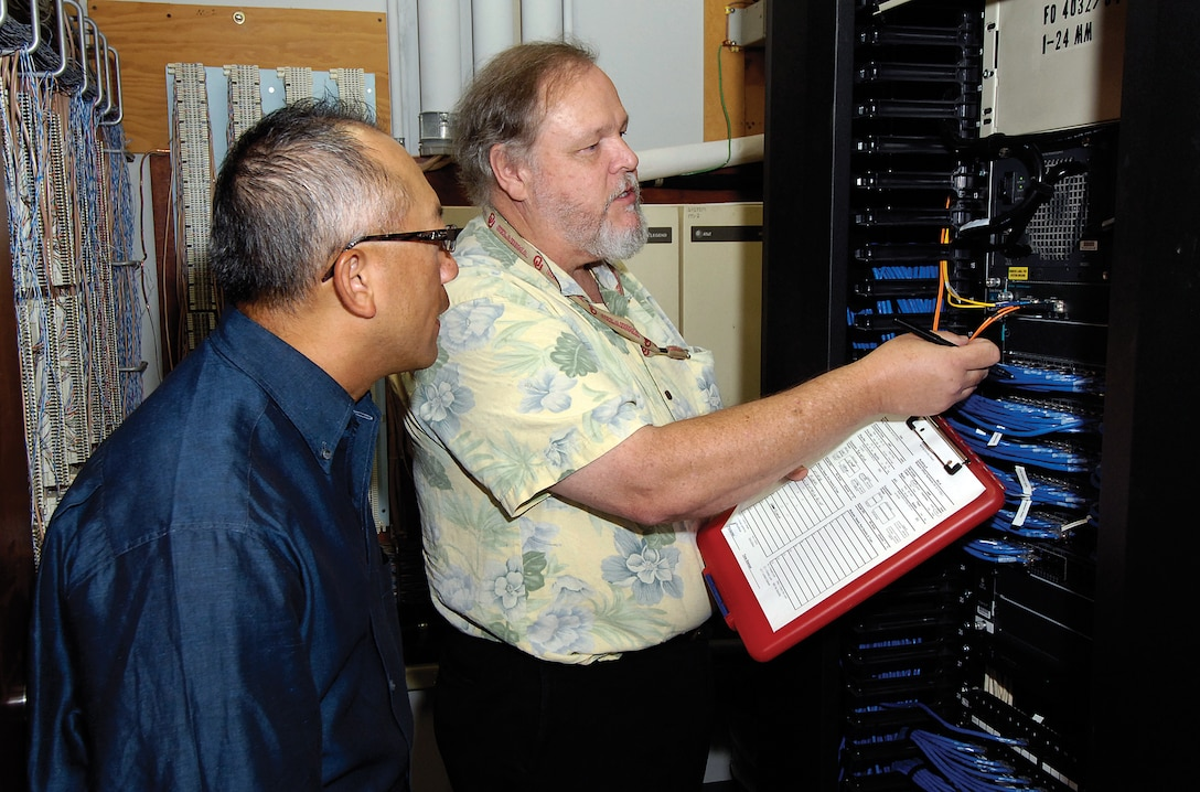 Fred Peake, right, a 38th Cyberspace Engineering Group systems telecommunications manager, reviews with Thanh Alcorn, a Network Branch lead engineer in the 38th Engineering and Implementation Division, how to verify devices on the network. Six teams of two recently began this task which will take them to more than 300 such communications closets across base. (Air Force photo by Margo Wright)