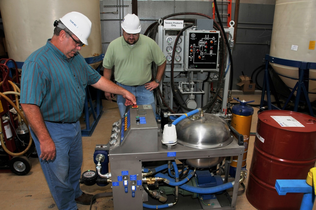 From left, Bill Hane, ATA outside machinist, and Casey Schewe, ATA conditioned-based maintenance engineer, inspect a portable processing unit at the Oil Processing Facility prior to deployment. These small units are delivered to a piece of equipment to remove water and particulate contamination from its oil without removing the oil from the equipment. (Photo by Rick Goodfriend)