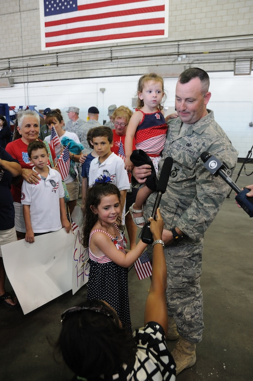Technical Sergeant Stephen Tibbetts and his daughters, Gemma and Sophia, look on with amazement as their dad is being interviewed by reporters following a send-off ceremony held August 9, 2010. Approximately 40 Security Forces airmen are scheduled to deploy to Iraq for approximately 6 months. (U.S. Air Force photo/Master Sergeant Sandra Niedzwiecki)