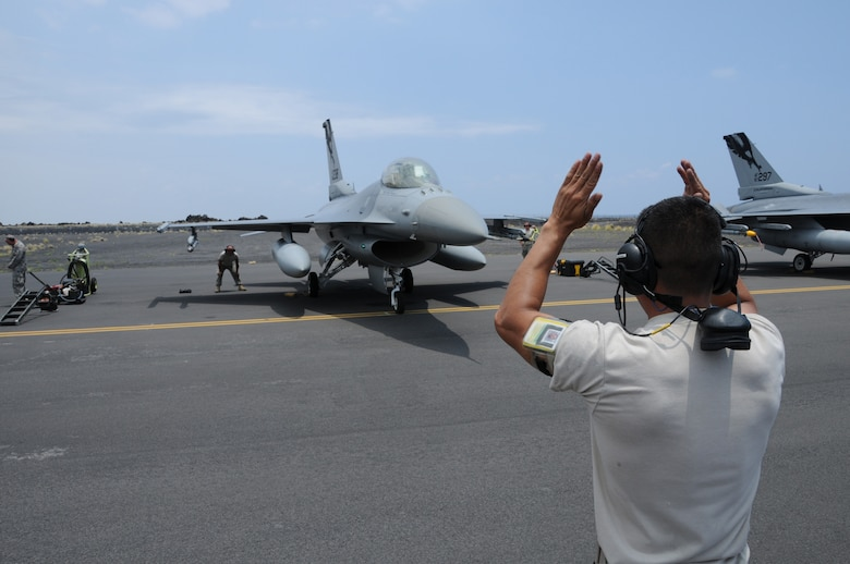 U.S. Air Force Staff Sgt. Jesus Mata marshalls in his F-16C Fighting Falcon from the 144th Fighter Wing, Fresno, Calif. after a successful mission in support of the Rim of the Pacific exercise on July 13, 2010 at the Kona International Airport, Hawaii.  RIMPAC is a biennial exercise that promotes interoperability involving people and assets from 14 different nations.  (U.S. Air Force photo by Senior Master Sgt. Chris Drudge/released)